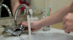 Washing hands in lavatory basin - stock footage