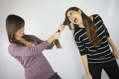 Girl pulling the hair to another girl that shouts Stock Photos