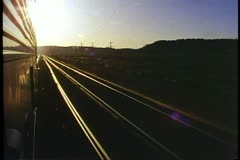 POV out of train window, passing view, sunset, electrical poles passing Stock Footage