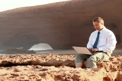 Businessman working on laptop on beautiful Legzira beach Stock Footage