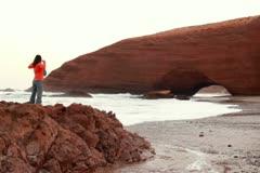 Successful woman raising hands on beautiful Legzira beach Stock Footage