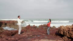 Couple standing with crossed hands on the beach Stock Footage