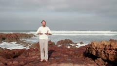 Man doing breathing exercises on Legzira beach Stock Footage
