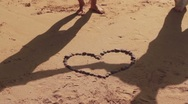 Silhouettes of couple holding hands in heart shape with stones on the beach Stock Footage