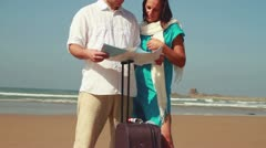 Couple with valise having fight over map on the beach, steadicam shot Stock Footage
