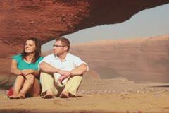 Couple in love sitting on beautiful Legzira beach, dolly shot Stock Footage