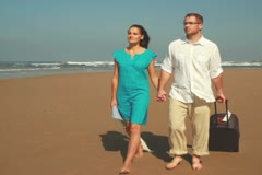 Couple with valise walking on the beach, steadicam shot Stock Footage