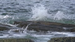 Rocky coastline. Slow motion wave submerging rocks - stock footage