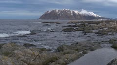 Rocky shoreline in Norway. Slow motion waves with snowy island Stock Footage