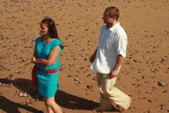 Man proposing marriage to surprised woman on the beach, steadicam shot Stock Footage