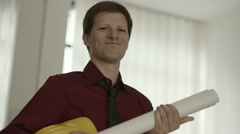 Architect with building plans smiling at camera Stock Footage