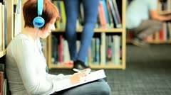 Female student listening to mp3 player in college hub  Stock Footage