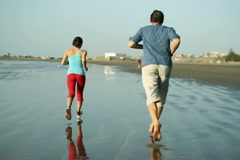 Young sport couple jogging on the beach, slow motion NTSC Stock Footage