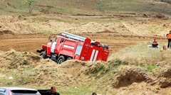 Firetruck on rally cross track in russian province wets the road to prevent dust Stock Footage