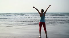 Woman's silhouette on the beach with her hands raised, slow motion HD Stock Footage