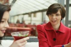 Kaksi naispuolista kaveria juominen cocktaileja ja jutteleminen bar, steadicam a Arkistovideo