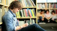 Male classmate networking online in college hub  Stock Footage
