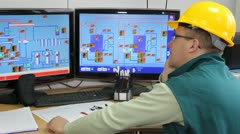 Industrial worker in control room - stock footage