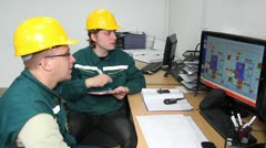 Industrial workers in control room - stock footage