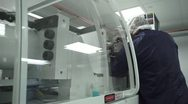 Man Reaching Into Machine in Cleanroom Stock Footage