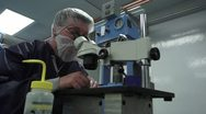 Low angle of Technician in Clean Room looking in Microscope Stock Footage