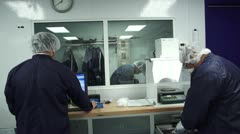 Technicians preparing to work in Cleanroom - stock footage