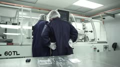 Two Technicians work together in Cleanroom - stock footage
