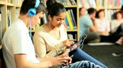 Young students study and listening to mp3 player   Stock Footage
