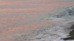 Water breaking on beach at sunset Stock Footage