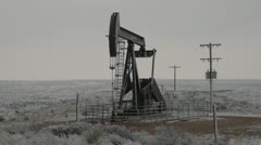 Texas oil derrick donkey pump in snow Stock Footage