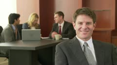 Portrait of business executive with conference in background - stock footage