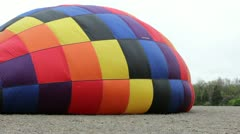 Hot air balloon laying in field Stock Footage