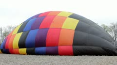 Hot air balloon being filled in field Stock Footage