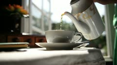 Pours tea into cup on background of rays sun Stock Footage