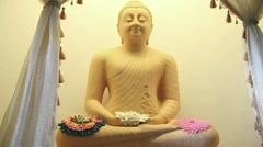 Puts petals of flowers to the statue Buddha Stock Footage
