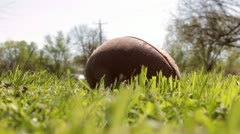 Football in grass with cars driving by Stock Footage