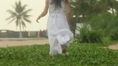Woman in a dress running barefoot on green grass Stock Footage