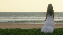 Woman in a dress standing on the shore of the ocean Stock Footage