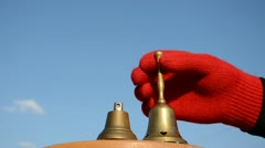 Hand with brass bell and  sky Stock Footage