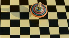 Wooden whirligig rotate on chessboard Stock Footage