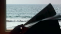 Reading book on background of the ocean near a window - stock footage