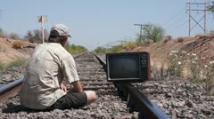 Man Sitting on the Railway Tracks With an Old, Retro TV Stock Footage