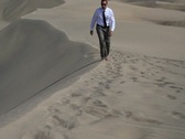 Young businessman walking on the desert NTSC Stock Footage