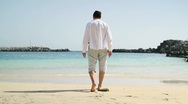Young man walking on the beach HD Stock Footage