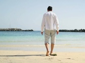Young man walking on the beach NTSC Stock Footage