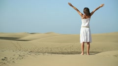 Woman in the desert with arms outstretched HD - stock footage