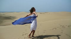 Carefree young woman running with blue sarong in the desert, slow motion  HD Stock Footage