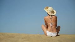 Sexy woman in summer hat and bikini sitting on the beach HD Stock Footage