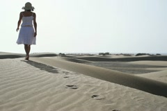 Woman in white dress and summer hat walking on the beach NTSC Stock Footage