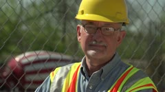 Construction worker on site, looking at camera, close up - stock footage